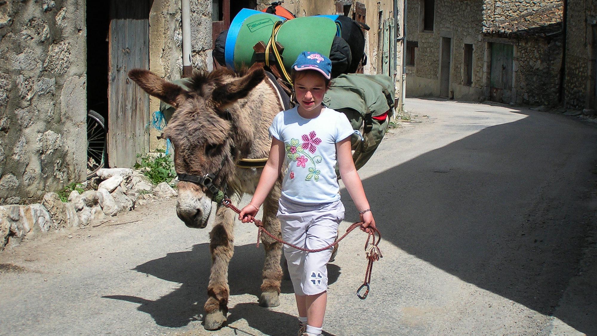 Traversée de village lors d'une rando en famille avec des ânes